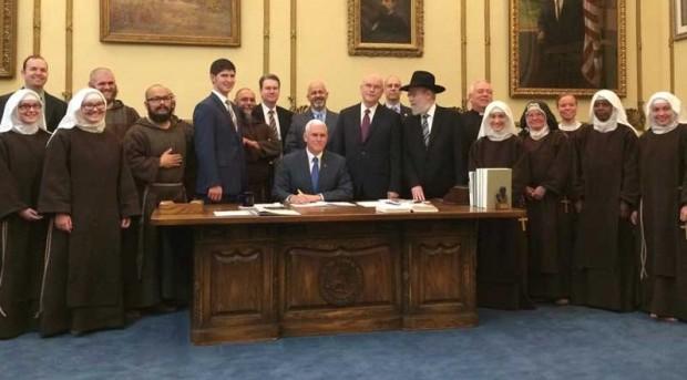 O governador Mike Pence, rodeado por religiosos, ao assinar polêmica lei na quinta-feira. (Foto: Divulgação)