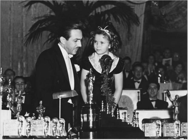 """Na cerimônia do Oscar de 1939, Walt Disney recebe da atriz Shirley Temple uma estatueta especial por """"Branca de Neve e os Sete Anões"""". O  desenho não foi indicado ao Oscar de melhor filme, apesar de ser um sucesso de crítica e público. (Foto: Corbis)"""