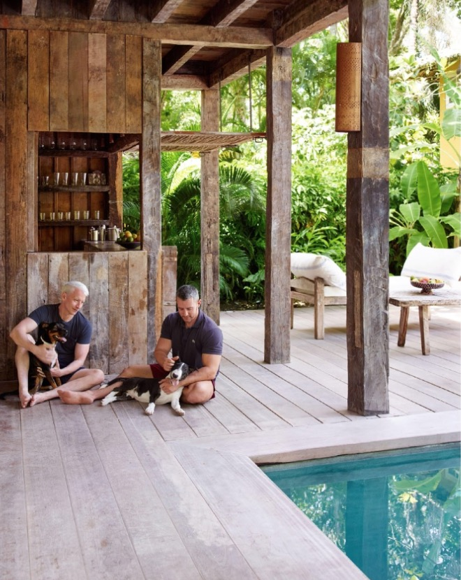 O jornalista com o namorado, o empresário da noite Benjamin Maisani, brincam com os cachorros do vizinho na varanda da casa principal. (Foto: Reprodução)