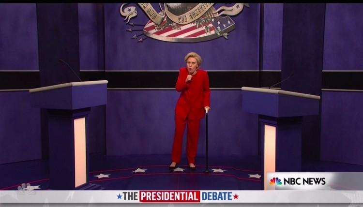 Hillary Clinton (Kate McKinnon) entra de bengala e tossindo muito no debate, zombando de sua recente pneumonia. (Foto: Reprodução)