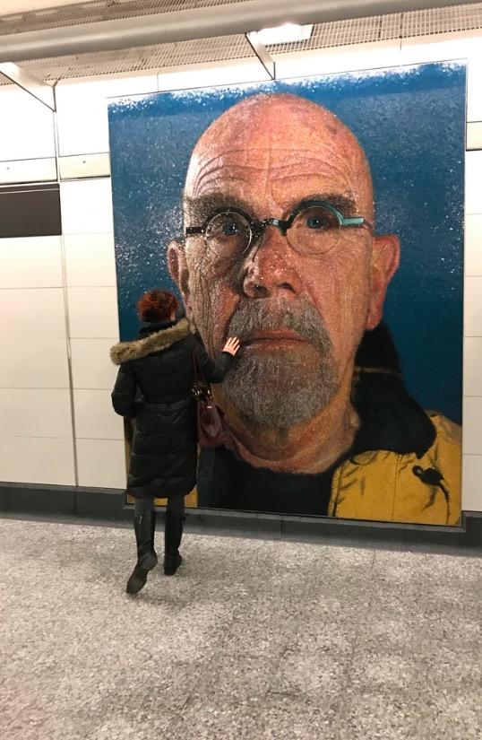 Visitante toca o auto-retrato do artista Chuck Close. (Foto: Marcelo Bernardes)